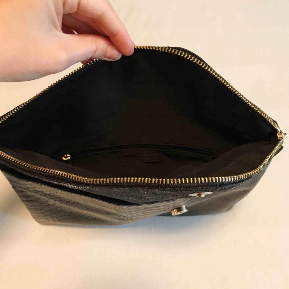 Riktigt snygg clutch väska! Svart med krockodilmönster och gulddetaljer. Rymmer allt det viktiga man behöver när man ska iväg, mobil, plånbok, nycklar, hörlurar, mindre necessär osv. Väldigt rymlig för att vara en mindre väska! Mycket fint skick!. Väskor.