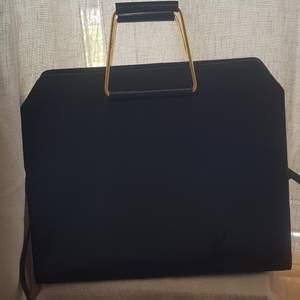 Stor väska med gulddetaljer från Asos, något nött på handtagen