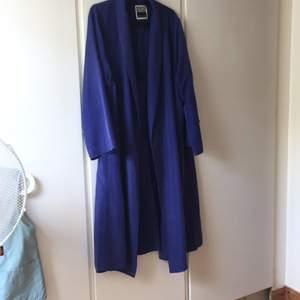 En snygg kornblå kappa från Weekday, köpt här på Plick. Den går ner till anklarna på mig som är 156cm. Ett litet hål i innerfickan, går att sy ihop. Finns katter i hemmet. Frakt 79kr