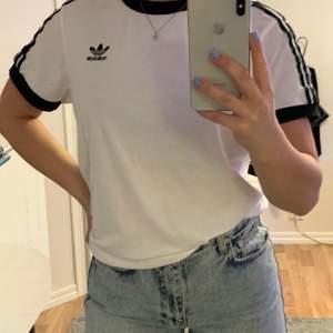 Adidas t-shirt med tre streck på ärmarna. I bra skick🥰 Nypris 299kr, säljs för 150kr💓 Köparen står för frakten +63kr. Betalning sker via swish💗