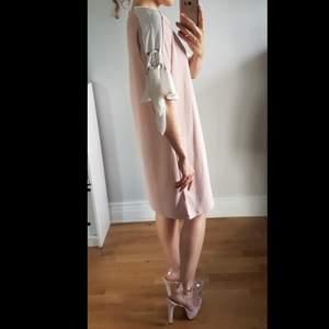 Klassisk, feminin, Italien-inspirerad festklänning av Chiara Forthi Milano, i dusty rose m vita ärmar & knytbara band genom silveröglor. Stilren & festlig. Frakt tillkommer 66 kr för spårbart paket. (Oanvänd av mig, endast provad för fotot)
