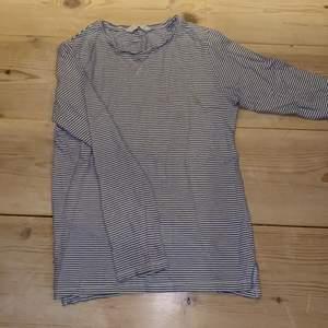 """Jättefin långärmad mango t-shirt vit med smala mörkblå ränder.🤍💙 Bra/acceptabelt skick då den har två små fläckar (se bild 3). Säljer pga för liten. (Storlek XXS/ 11/12 år, jag är XS/S). Superskön, mjuk och bekväm då det endast är 100% cotton/bomull. Passar bra till tex mörkblå jeans eller shorts. (Självklart stryker jag den innan försäljning) DM vid intresse/frågor/fler bilder.❣️(Det kan du göra här under där det står """"kontakta"""") Avhämtning på Södermalm eller frakt till självkostnadspris.:)"""