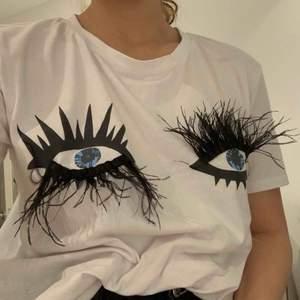 T-shirt med ögon och fjäderfransar Köpt i butik i Frankrike! Använt 2 ggr.  Funkar toppen för mig som har strl S😊