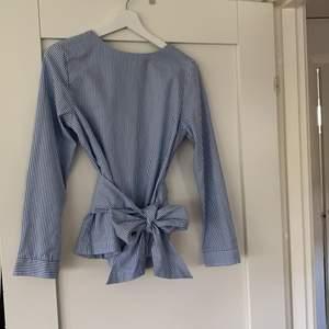 En härlig sommar blus med ett band som knyts i midjan, randig blus med en härlig färg💗 blusen är ifrån gant med storlek 34. Har knappt användt denna blusen skulle klassa den som splitter ny💗