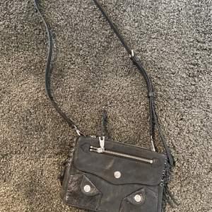 Svart handväska med silvriga detaljer från DKNY, köpt för cirka två år sen men i mycket bra skick men inte använd så mycket då jag inte har väska så ofta.