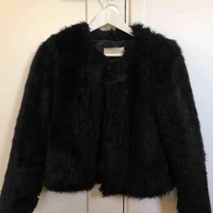 Säljer denna faux fur jacka från Stand. Storlek 34, svart färg. Nypris 2000kr, säljer för 250. Jackan är använd men fortfarande i ett fint skick!