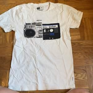 Denna T-shirt är helt oanvänd, jag använder den aldrig och därför ska den till ett nytt hem❤️ Tröjan har en 90 tals vibe, med en sterio och ett gammalt tape. Tröjan sälja för 140 inkl frakt!