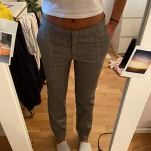 Jätte fina gråa kostymbyxor med röda rutiga detaljer. Jag är 157 och de går ner precis till mina anklar. De sitter lite långmidjat på mig då de är i storlek 36 och jag är 34. Frakt ingår inte i priset. Kan mötas i Stockholm södra.💕💕