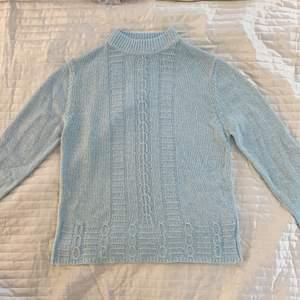 Ljusblå stickad tröja i strl S/M. Materialet är inte stickigt och i fint skick. Fina stickade detaljer.