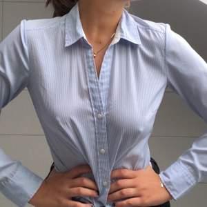 En ljusblå och vit, smalrandig skjorta från H&M. Superskönt material och snygg passform för kvinnor!