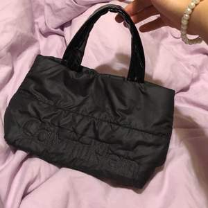 Liten puffig väska från Calvin Klein🖤 handtagen är lackliknande och väskan är typ fodrad. Ca 25 x 17 x 10 cm.  Bara att skriva om ni har frågor!!