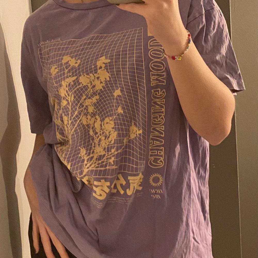 T-shirt i lila med gult tryck i urtvättad stil, i storlek M, köpt i somras, använt få gånger från pull & bear. Over size på mig som annars bär S . T-shirts.