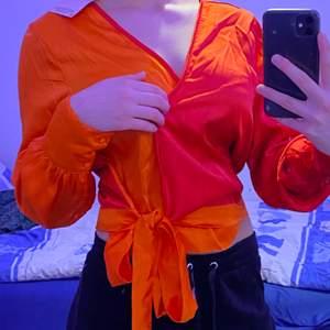 En helt ny och oanvänd skrik neon orange/röd blous som är väldigt öppen på framsidan och därför rekommenderar jag att man sätter den med en nål om man inte gillar att visa bröstsidan så mycket. Annars är den väldigt passande till fester och sådant. Materialet är underbart skönt. Storlek 40 men passar 38 också.
