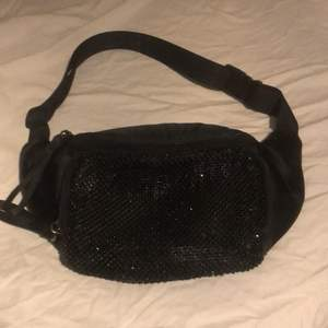 En magväska från Dondonna i svart tyg med glittriga stenar på. Justerbar midja. Helt oanvänd. Ny skick. Nypris 300kr.                                                                 Köparen står för frakt