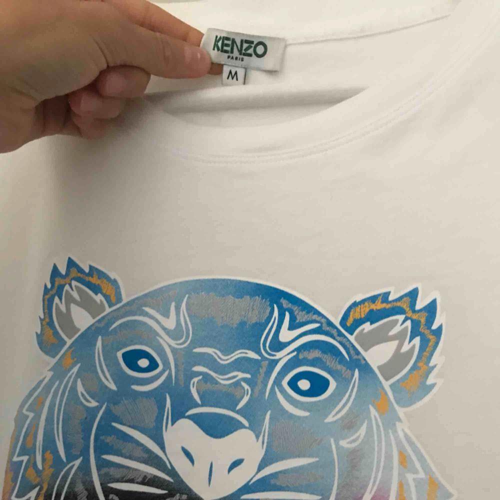Kenzo T-shirt använd på tok för lite därav säljer jag den. (Har inte bråttom med att sälja)  Storlek M men liten i storlek.  Nypris 999kr köpt på Nk i Göteborg förra året sen sommaren. . T-shirts.