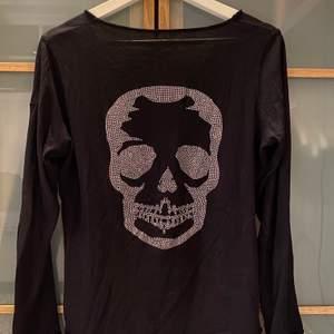 Svart långärmad tröja med döskalle tryck på baksidan. Tunt material, super skön på! Lite u ringad fram.