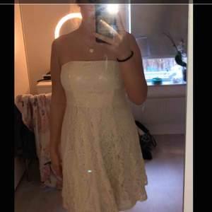 Fin klänning som passar nu till student eller skolavslutningar, den är vit med blommigt spets på. Köparen står för frakt:)