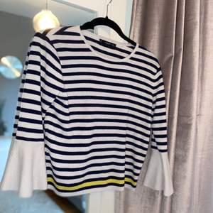 Randig tröja från MANGO med volangärmar. Lite kortare modell med en gul rand längst ned, övriga ränder marinblåa. Skriv för fler bilder