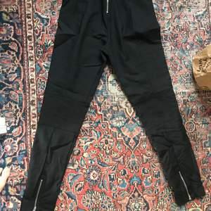Svarta snygga kostymbyxor från Tiger. Fint skick. Nypris 1300kr. Baksidan har dragkedjor vid anklarna och svanken.