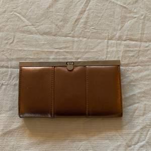 Kopparfärgad plånbok med många olika fack