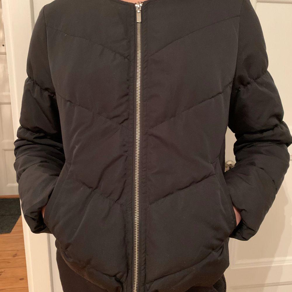 Svart tunnare dunjacka med blixtlås. Finns även två fickor. Säljs då den är för liten, helt felfri. XS. Jackor.