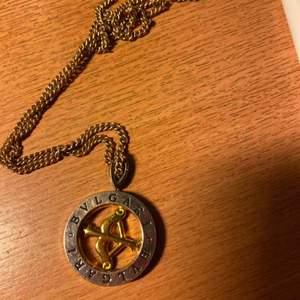 Bulgari halsband . Amor pil . Dubbla ringar str av en svensk femkrona. Guld o silver färgad. Frakt ingår i priset