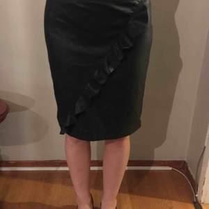 Svart kjol i läderimitation med en snygg volang framtill