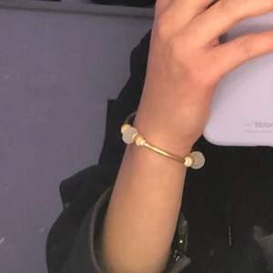sjukt fint guldigt armband med vita och rosa detaljer detaljer.