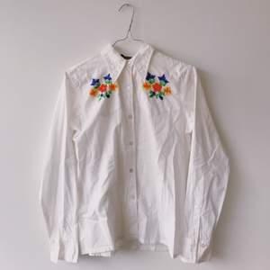 Superfin skjorta i 100% bomull med blom-brodyr på bröst och bak. Inköpt i liten butik i Italien men har tyvärr aldrig kommit till användning.