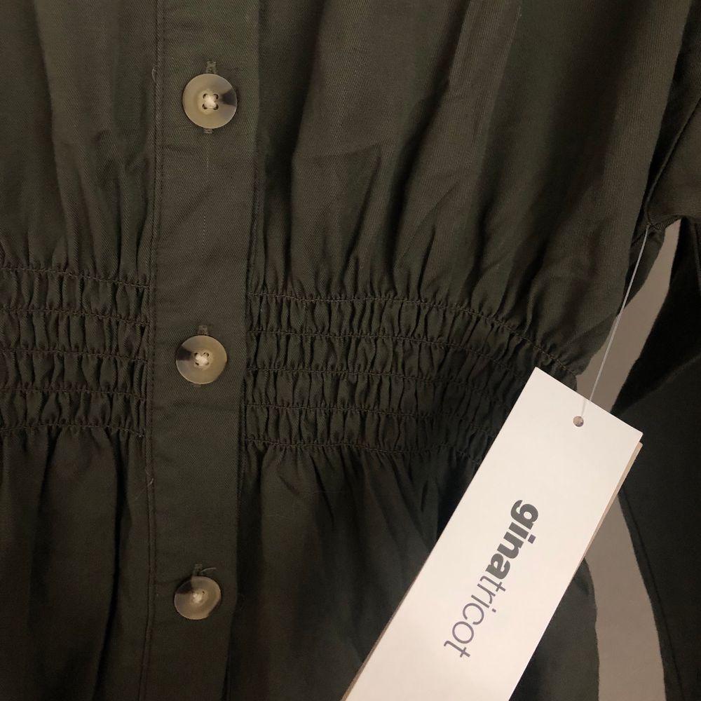 En militärgrön skjorta från Gina Tricot med smock detalj i midjan, för att skapa en fin figur. Strl 36. Helt oanvänd med prislapp kvar. Köpt för 350kr men säljer för 250kr + frakt. Önskas fler bilder är det bara att hojta till🌸. Skjortor.