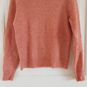 Rosamelerad stickad tröja i ull/akryl. Måttligt använd, lite noppig.
