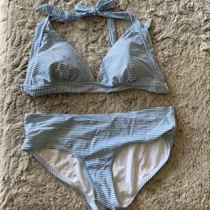 Blå och vitrandig bikini. Överdelen är i M och underdelen i S.