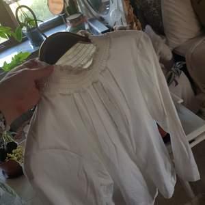 En lite gammledags vit tröja, med polokrage och detaljer runt bröst/axlar. Fantastiskt fin! Det står strl 42 i den men passar mig som har XS väldigt bra!  PRIS KAN DISKUTERAS, frakt tillkommer!🧡💜💙💗💚💓🧡💜🧡
