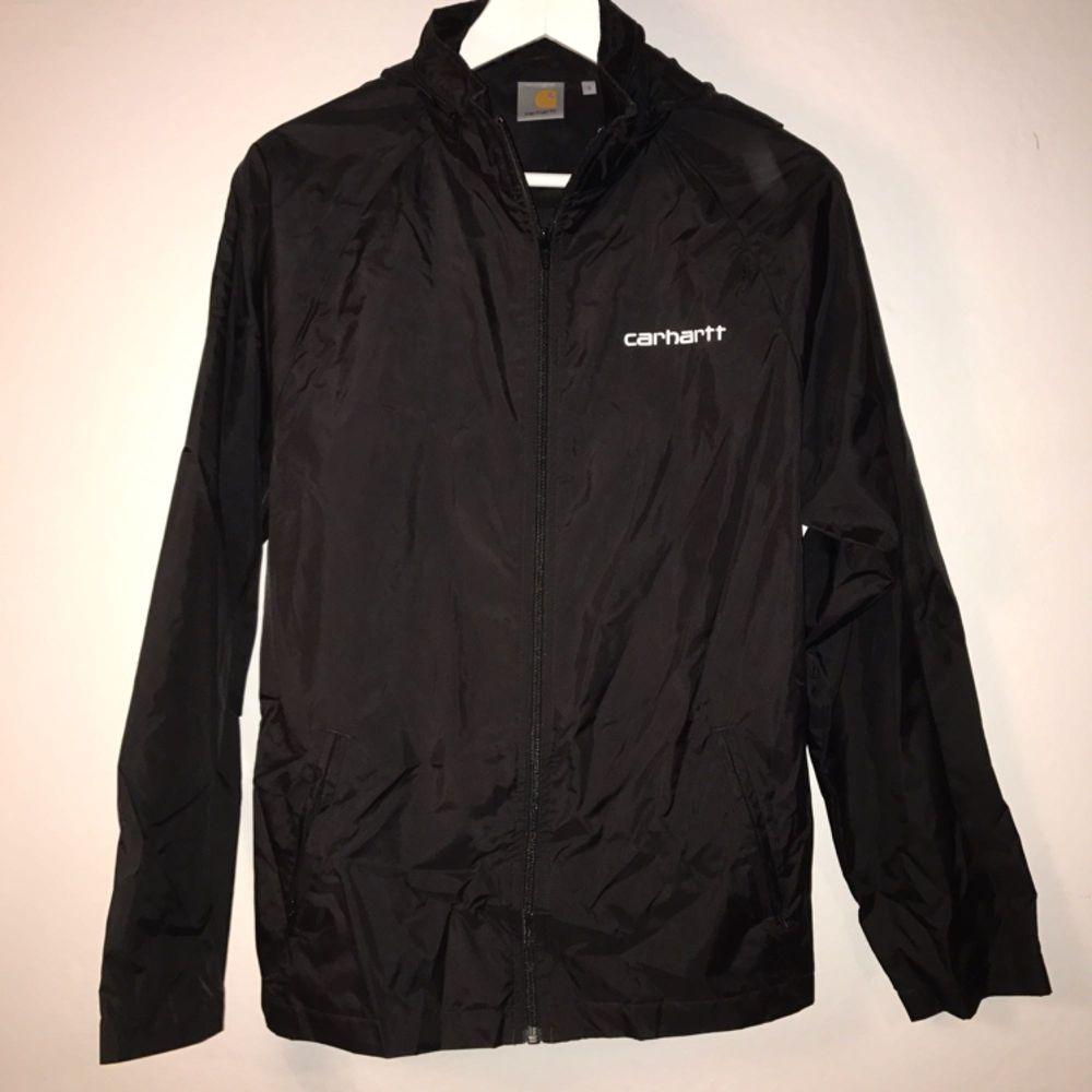 Oanvänd regnjacka i 100% nylon från carhartt. Crew tryck på baksida, åtdragbar + intagbar luva.  Stl är Unisex Small  www.carhartt.com. Jackor.