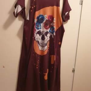 Snygg kort klänning med döskallemotiv fram . Fladdermus armar då ärmen sitter löst hängade. Jag har aldrig använt den utan köpte den i min tur och den passar inte. Storleken är L / XL och kan passa xxl också då den är Lite vid.Bak på ryggen är det mönster som ser ut som ryggraden.  80 kr med frakten inräknat.