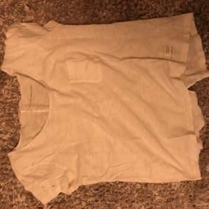 Tshirt med en liten ficka och fina detaljer. En rosett på basidan av tröjan längst ner.