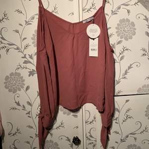En mörkrosa blus från nakd med alla lappar kvar, fina detaljer på ärmarna
