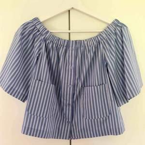 Blå & vitrandig blus från monki strl xs. Knappt använd. Off shoulder. Resår i halsen.