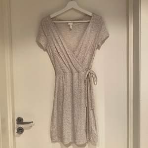 Omlottklänning med prickigt mönster.