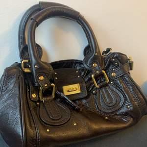 Köpt på secondhand, därmed troligtvis ej äkta. Fin vintage handväska med guldiga detaljer. Lite sliten som man kan se i tredje bilden, annars en jätte fin väska! Lås och nyckeln medföljer