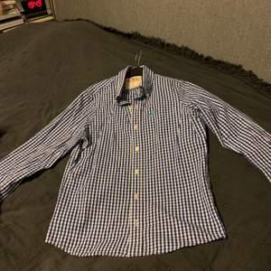 """Blå/vit rutig Holister skjorta. Väldigt fräsch, använd vid få tillfällen. Stl. S, ärmlängd 66 cm, rak """"killmodell""""."""