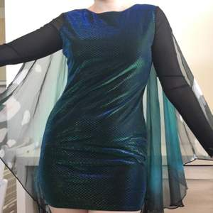 The label is cut off but it fits size M/L. The length from neck down is size 75cm. Dress has been used twice, and one of the arms has been a little damaged around the hand/wing, but it seems easy enough to sew together! The dress has a black colour with shimmering dark blue and dark green. The arms are half transparent and the wrists connect decorated butterly