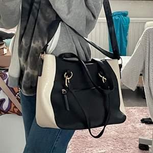 """En svart vit väska i nytt skick då den bara har använts endast 2 gånger. På sidan av väska är det vitt """"ormskinn"""" och den svarta delen är det fake skinn. Den har även långa samt korta band"""
