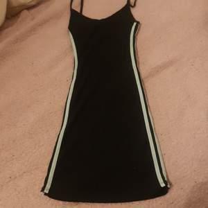 En svart väldig fin klänning med 2 vita streck på sidan. Får super fin form i den.
