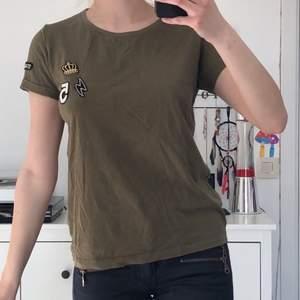 army grön t-shirt med broderade detaljer. Passar storlek S och XS. Välanvänd och i bra skick. Frakt förekommer beroende på hur många plagg man köper.