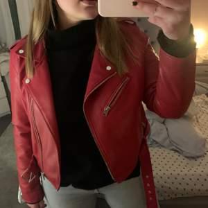En jättefin skinnjacka med en ganska klar röd färg. Jackan är i storlek L men sitter som en S.