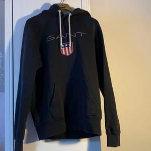 Svart hoodie från Gant. Ett igensytt hål på höger arm men utöver det bra skick. Storlek S