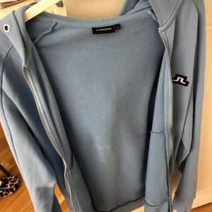 Säljer denna fina ljusblåa hoodie från J.Lindeberg. Använd två gånger. Ge förslag på pris. Storlek S