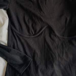 Svart långärmad ribbad tröja med markeringar under brösten från Gina! Stretchigt material, superskön🤍 Storlek s! Aldrig använd, superbra kvalitet