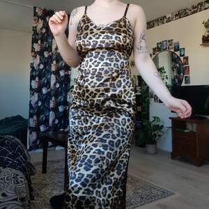 Leopard klänning med slittar på båda sidorna där nere. Jag är ungefär 173cm och den kommer till anklarna på mig. Justerbara band och stretchig i midjan så lätt att få på sig! Du får det billigare om du köper fler plagg!